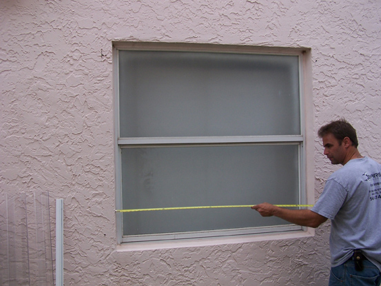 >Measuring the width of your window's rough opening.